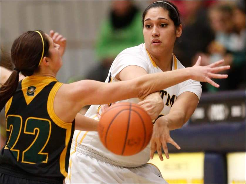 Whitmer's Abigail Sarabia (40) passes around Clay's Samantha Enck (22) during the first quarter.