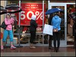Shoppers stand outside the Kate Spade store at St. Louis Premium Outlets in Chesterfield, Mo. on Dec. 22.