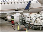 A worker prepares to fuel a United Express aircraft after it arrived at Dallas-Fort Worth International Airport. The money airlines will save this year through less-expensive jet fuel won't be passed on to fliers to encourage them to buy tickets because many flights already are full.