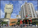 Tourists gather in front of old and new Casino Lisboa during a Chinese New Year celebration in Macau, which has become a tourist mecca for gambling at the city's 30 casinos.
