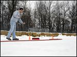 Tony Nastale, ice manager, sweeps snow off the outdoor ice rink. In addition to the rink, the bowling alley, 2345 W. Dean Rd. in Temperance, has an outdoor bar area, fire pits, and sand volleyball courts. Mr. Kenny plans to add more activities soon.