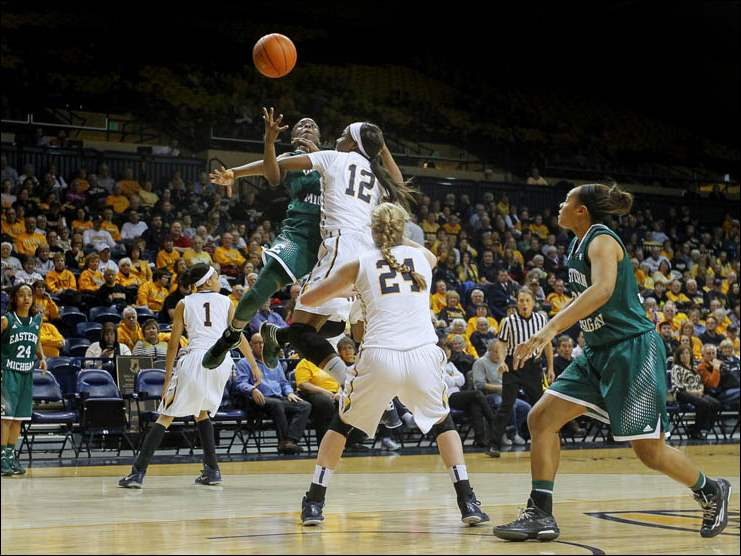 University of Toledo basketball player Janice Monakana (12) fouls Eastern Michigan University player Jamaica Bucknor (15).