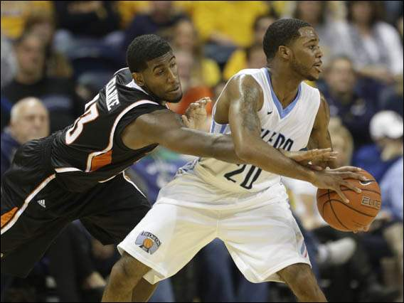 University of Toledo basketball player Julius Brown (20) passes the ball away from Bowling Green State University basketball player Jehvon Clarke (23).