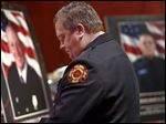 Toledo Firefighters Local 92 President Jeffrey Romstadt pauses during a memorial service on Monday.