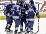 The Walleye's Justin Mercier, center, celebrates his goal in the first period of a victory over Wheeling. The forward had two goals and an assist as Toledo moved into a first-place tie in the ECHL North.