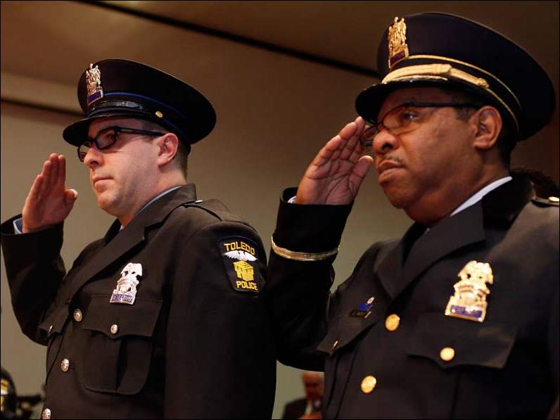 Toledo Police Officers Brian Smith, left, and Capt. Benjamin Tucker, right, salute the flag during their promotion ceremony at One Government Center.