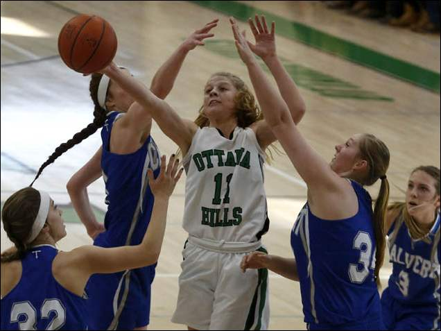 Ottawa Hills' Allison Dewire is surrounded by Tiffin Calvert defenders as she reaches for a rebound.