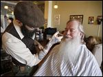 Tyler Anderson trims the mustache and beard of Paul Neumann of Vernon Hills, Ill., at Beardsgaard Barbers in Batavia, Ill.