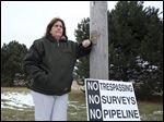 Laura Cole displays a sign to show her displeasure with plans to route a gas pipeline near her Swanton property, which she hopes to develop into a working farm for autistic residents.