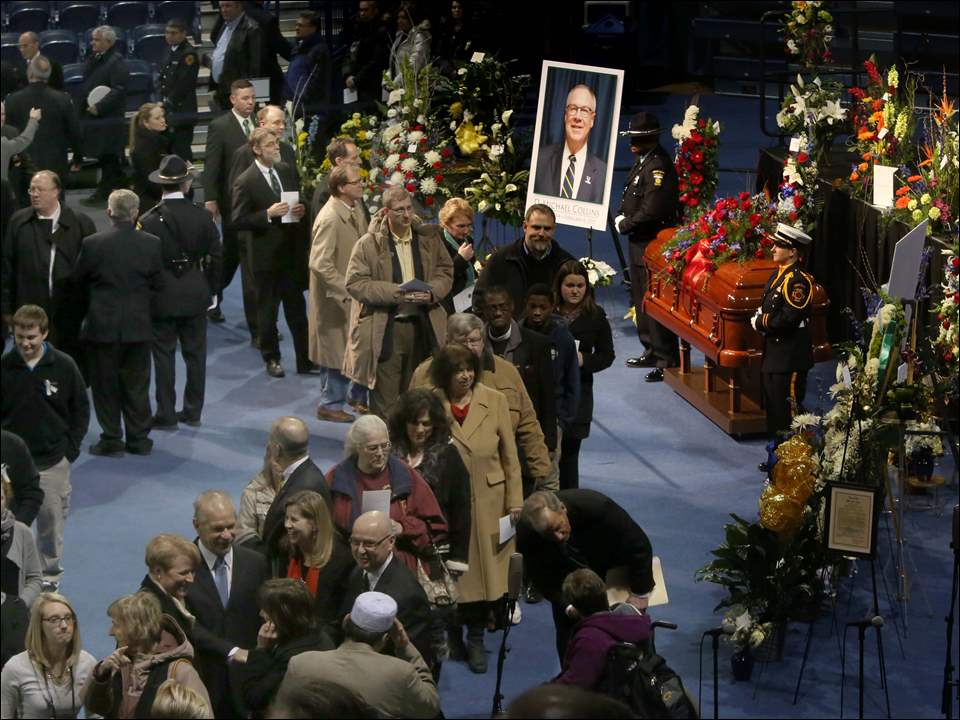 Mourners file past the closed casket of Toledo Mayor D. Michael Collins before his memorial service.