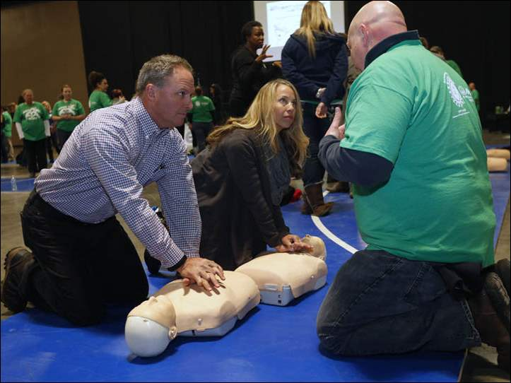 Tim and Laurie Mulligan learn hands-on CPR from Toledo firefighter Jason Hart during Save the Beat CPR training at the Seagate Centre in Toledo, Ohio