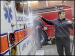Sylvania Township firefighters Craig Koperski, left, and Tyler Bellman, right, wash down their EMS truck, which is owned by Lucas County, in 2015.