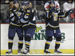 Toledo Walleye player Kyle Bonis (28) celebrates his goal with teammates Josh Holmstrom (22) and Cody Lampl (32).