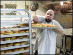 Bryan Bachli, chief donut officer at Bakery Unlimited, places freshly fried paczki's on a cooling rack at Bakery Unlimited.