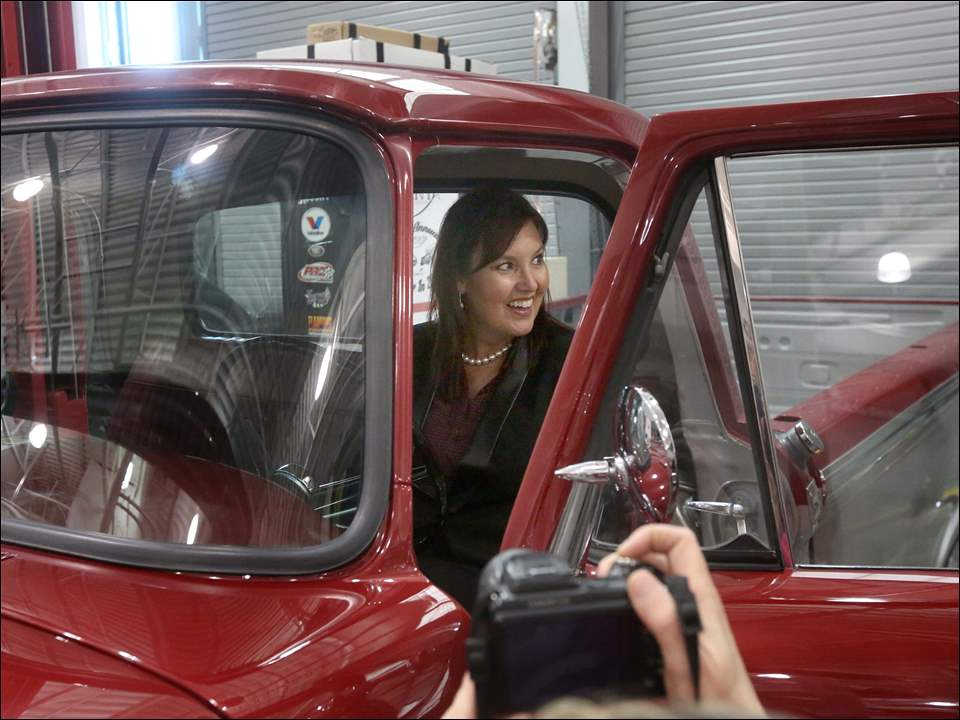 Lieutenant Governor Mary Taylor smiles as she takes a look inside a 1965 Ford that had been restored by students.