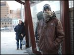 Jeffrey Adkins of Toledo shields himself from the cold weather while waiting for a bus Friday on Jackson Street in Toledo.