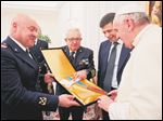 Italian Coast Guard officers give Pope Francis a cross made with wood from migrants' boats Wednesday at the Vatican.
