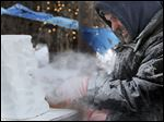 Danny Bloss of Niles, Mich., begins to craft his sculpture during the  this year's Winterfest in Perrysburg. In additionto the ice-carving competition, stores throughout Levis Com-mons also pitched in with crafts for children. Wintefest activities continue through Sunday.