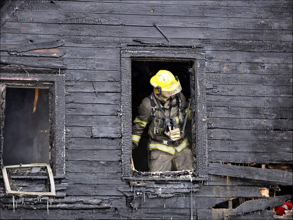 A member of Toledo Fire & Rescue looks through the burned window frame while responding to a fire located at 2414 Lawton Ave. on February 16, 2015.