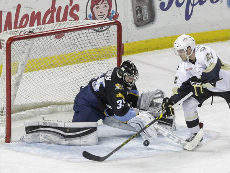 Toledo Walleye goalie Neil Conway (35) stops a shot by Wheeling Nailers player Jean-Sebastien Dea (21).