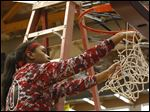 Rogers' Akienreh Johnson cuts down the rest of the net after defeating Start in the City League title game at Waite High School in Toledo.