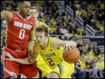 Michigan guard Spike Albrecht drives against Ohio State guard D'Angelo Russell during the first half on Sunday. Albrecht and Russell each scored 16 points for their teams, although Albrecht had a much bigger impact on the game than the more highly-touted Russell.