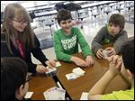 McCord Junior High and Sylvan Elementary School robotics team members Bailey Gillen, 13, left, Sydney Gillen, 10, center left, Noah Archer, 11, center, Kyle Rose, 11, center right, Mitchell Conant, 10, right, joke as they play cards at McCord Junior High in Sylvania Tuesday.