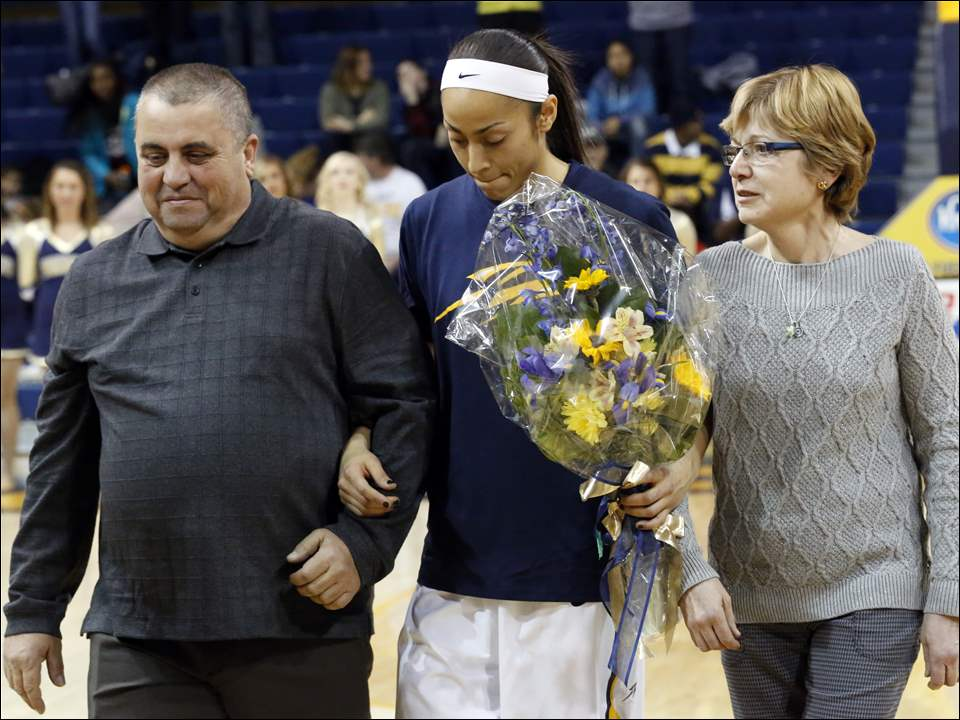 Inma Zanoguera is escorted onto the court by her parents Tomeu Zanoguera and Magdalena Zanoguera during the senior day event.