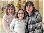 Sydney Hugo, a fourth grader with Dandy-Walker syndrome, is flanked by Jennifer Perry, left, and Jackman Road Elementary principal Sherry Farnan.