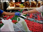 A shopper pays for produce at a Farmers Market in downtown Los Angeles.