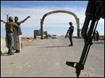 Afghan security police stand guard at checkpoint in Helmand province, south of Kabul, Afghanistan, Thursday.