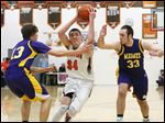 Sylvania Southview's Ben Casanova (34) drives to the basket against  Maumee's Austin Calopietro (13) and Jared Schriner (33) during a basketball game last Friday.