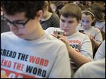 Eighth graders Craig Latty, left, Austin Nye, center, and Allie Walters quickly send text messages with classmates at Monroe Middle School to try to set a record.