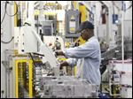 GM employees work the assembly lines putting transmissions together at Powertrain on May 10, 2011.