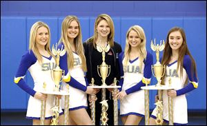 Senior members of St. Ursula Academy's dance team — from left, Madison Walsh, Melissa Wittenmyer, coach Erin Parseghian, Caroline Kelley, and Lexi Hicks — hold their trophies.