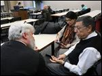 Ed Heilman, pastor of the Park Congregation United Church of Christ, Dr. Samina Hasan of the United Muslim Association of Toledo, and Behrooz Modarai of the Bah‡a'i Faith, talk before a Feb. 27 screening of 'To Light A Candle' at the University of Toledo.