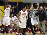 The Central Catholic bench and coach Nick Lowe react to a 3-pointer by Marcus Winters (3), who made five 3-pointers and scored 17 points to lead the Irish past Whitmer.