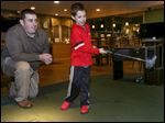 Golf instructor Matthew Lake, who is deaf, gives lessons to Evan Brown, 6, at the Bedford Hills Golf Club in Bedford Township, Mich. Evan has a low muscle-tone condition.