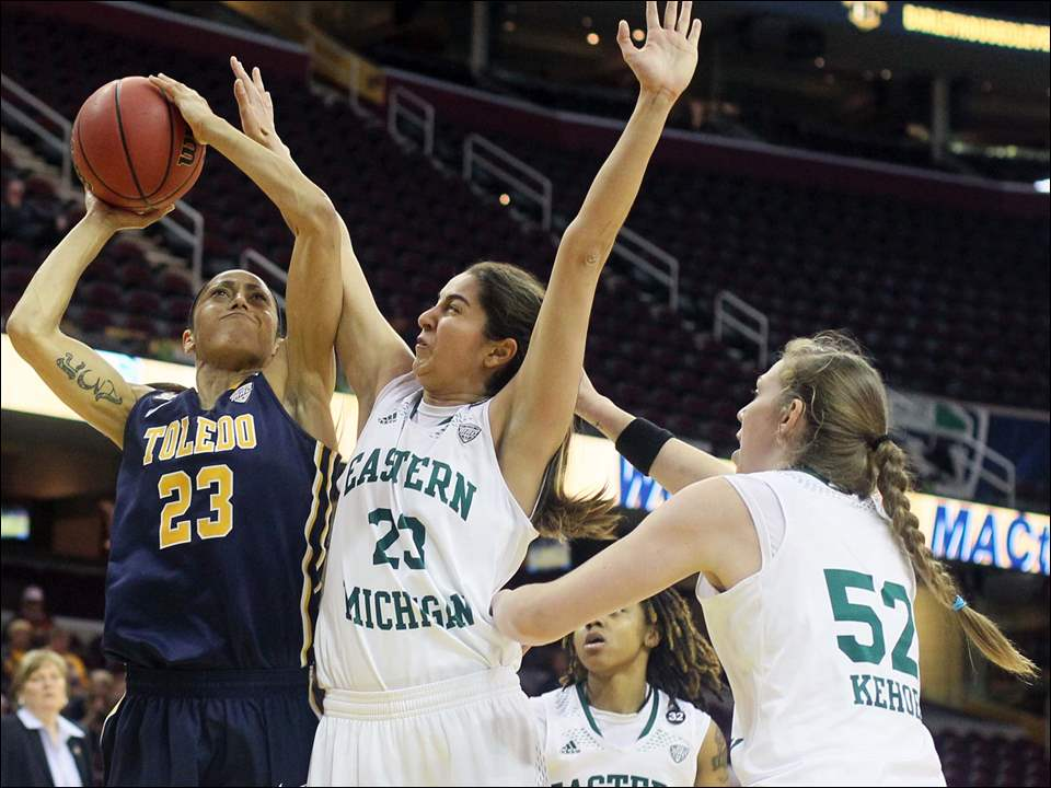 University of Toledo guard Inma Zanoguera (23) shoots against  Eastern Michigan guard Sera Ozelci (23) and center Rachel Kehoe (52).