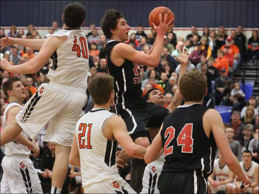 Cardinal Strich's Austin Adams (21) pushes past Gibsonburg defenders to drive in for a layup during the second quarter.