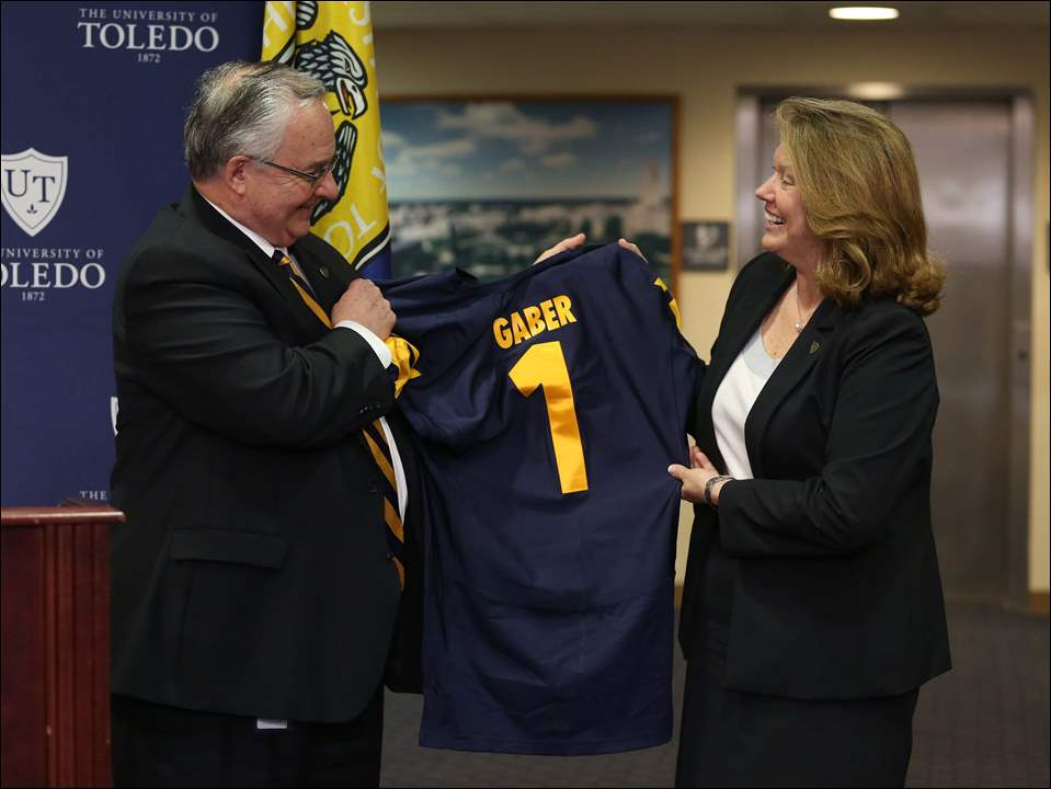 University of Toledo board chairman Joseph H. Zerbey, IV presents a personalized jersey to Sharon Gaber.