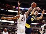 Illinois' Malcolm Hill (21) blocks a shot by Michigan's Max Bielfeldt (44) in the second half of an NCAA college basketball game in the second round of the Big Ten Conference tournament, Thursday, March 12, 2015, in Chicago. (AP Photo/Charles Rex Arbogast)