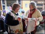 Becky White-Schooner, left, looks at Karen Wood's apron during a program on aprons at Carter Historic Farm near Bowling Green.