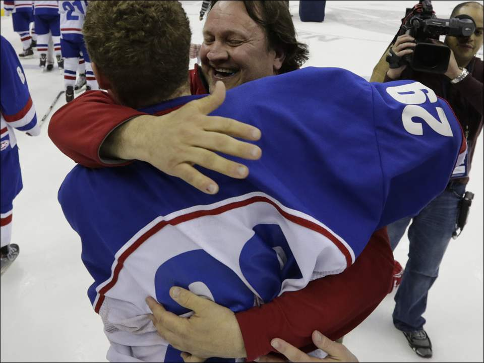 St. Francis de Sales hockey head coach Chris Varga hugs goalie Kade Phipps (29).