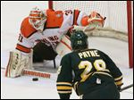 Bowling Green goalie Tommy Burke blocks a shot in front of Northern Michigan's Robbie Payne in the second period.