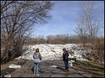 Tiffany Whitehead, left, from Adrian,  and Pam Davis, right, from Perrysburg, look at the ice accumulation at the entrance to Buttonwood Park during an outing on a sunny Sunday afternoon.