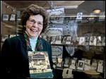Local historian Trudy Urbani holds a book she published on the Bedford Township area in front of the display she assembled at the Bedford Branch Library.