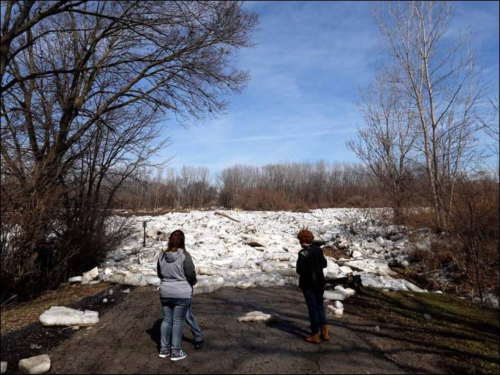 Tiffany Whitehead, left, of Adrian, Mich., and Pam Davis, right, of Perrysburg, look at the ice accumulation at the entrance to Buttonwood-Betty C. Black Recreation Area Sunday.