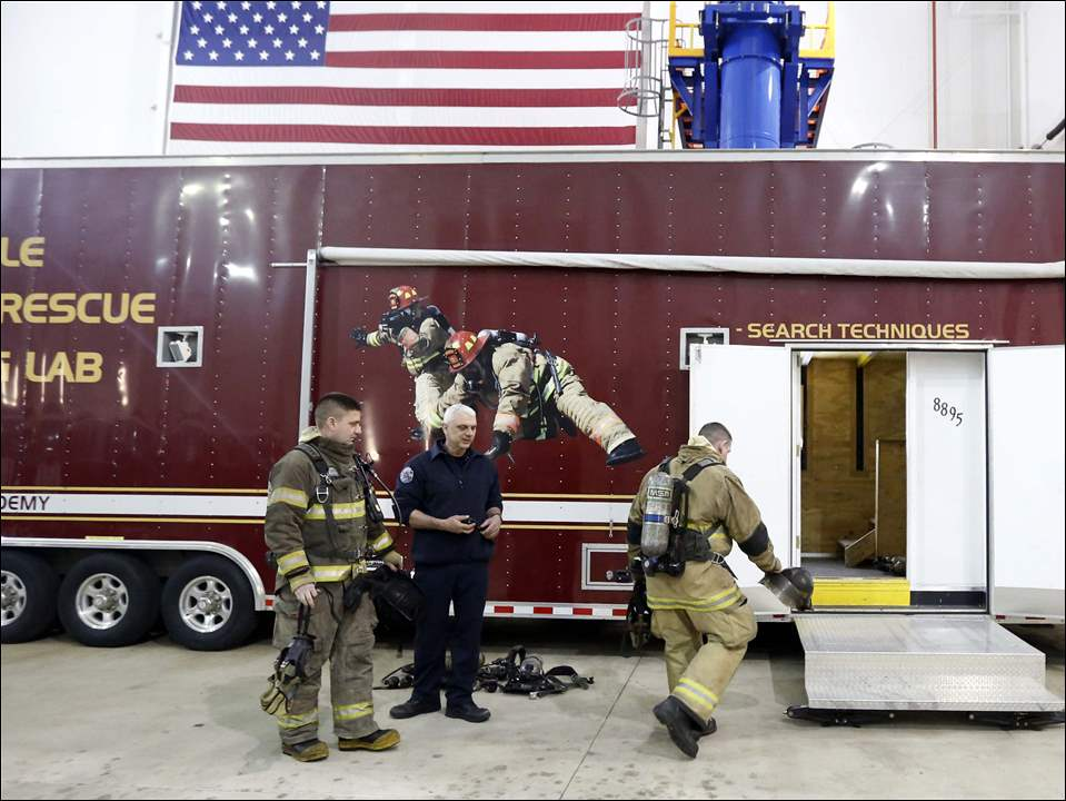 Lt. Greg Yingling, a Toledo firefighter, center, helps Firefighters Sterling Rahe, right, and Mark Wietrzykowski, left, get ready to do a training demonstration in the Mobile Search & Rescue Training Lab at Owens Community College.