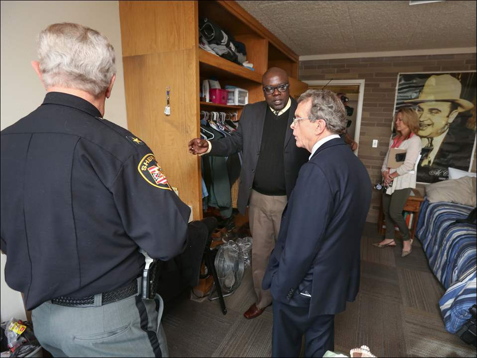Tachumbi Williams, a recovering heroin addict, center, shows Lucas County Sheriff John Tharp, left, and Ohio Attorney General Mike DeWine, right, his room at The Zepf Center Housing Center.